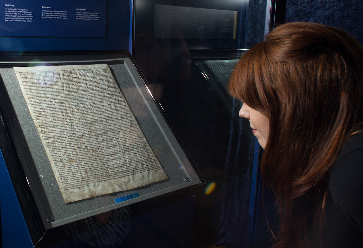 A visitor looks at the Magna Carta in Salisbury Cathedral's Cloisters and Chapter House in 2015. Photo by Matt Cardy/Getty