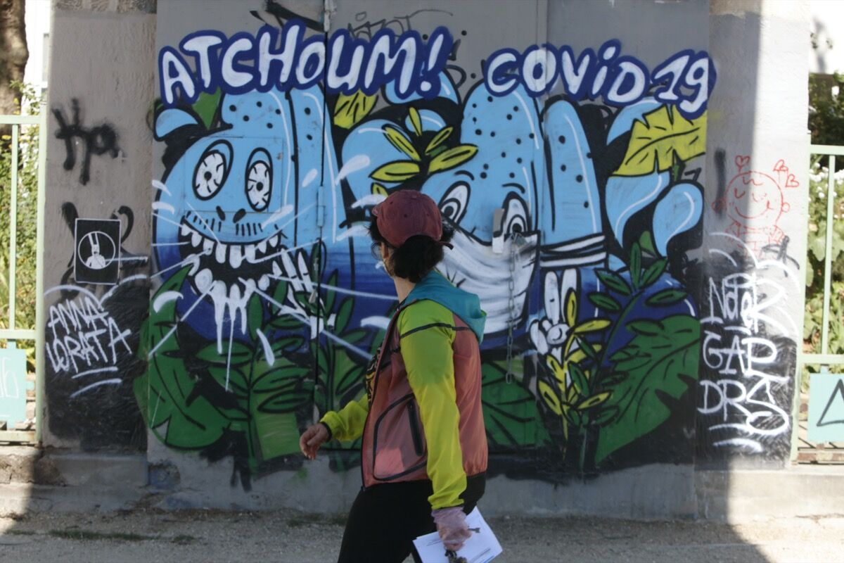 """A woman walks past a fresco mural with """"Atchoum! Covid 19"""" as the lockdown continues due to the coronavirus outbreak. Photo by Mehdi Taamallah/NurPhoto via Getty Images"""