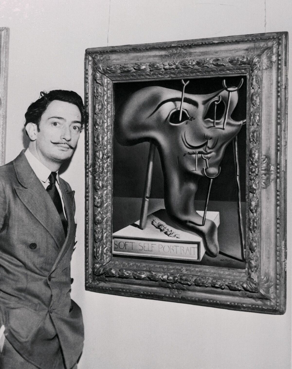Salvador Dali with his artwork Soft Self-Portrait at the Julien Levy Gallery, 1941. Photo by Bettmann / Contributor via Getty Images.