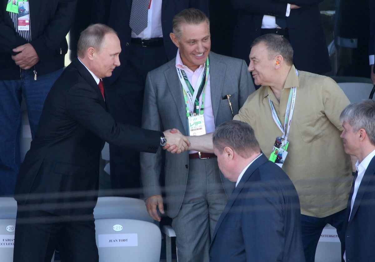 Russian President Vladimir Putin (at left) shakes hands with billionaire and businessman Arkady Rotenberg (at right) as his brother, Boris Rotenberg (at center) looks on. Photo by Mikhail Svetlov/Getty Images.