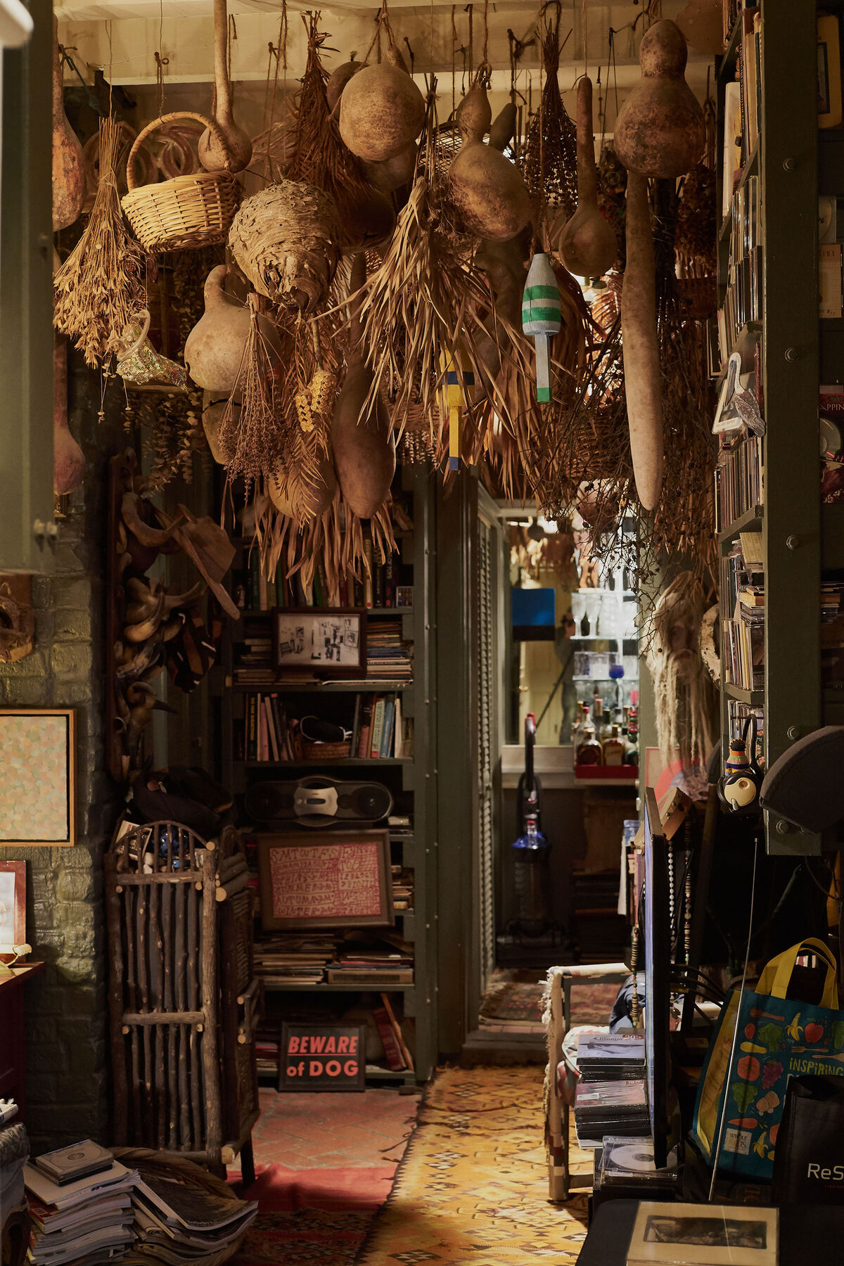 In Fagaly's study, an addition that connected two separate buildings in his home, gourds from the Melrose Plantation in Louisiana, where Clementine Hunter lived, hang from the ceiling, along with beehives, baskets, buoys, and palm fronds. Photo by Michael Adno for Artsy.