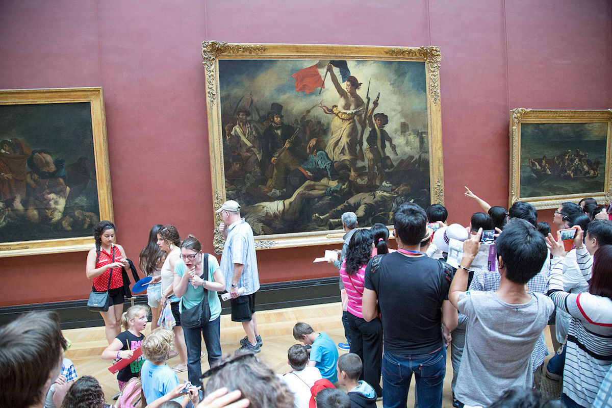 Eugène Delacroix's Liberty Leading the People (1830) on view at the Louvre. Photo by Victor Grigas, via Wikimedia Commons.