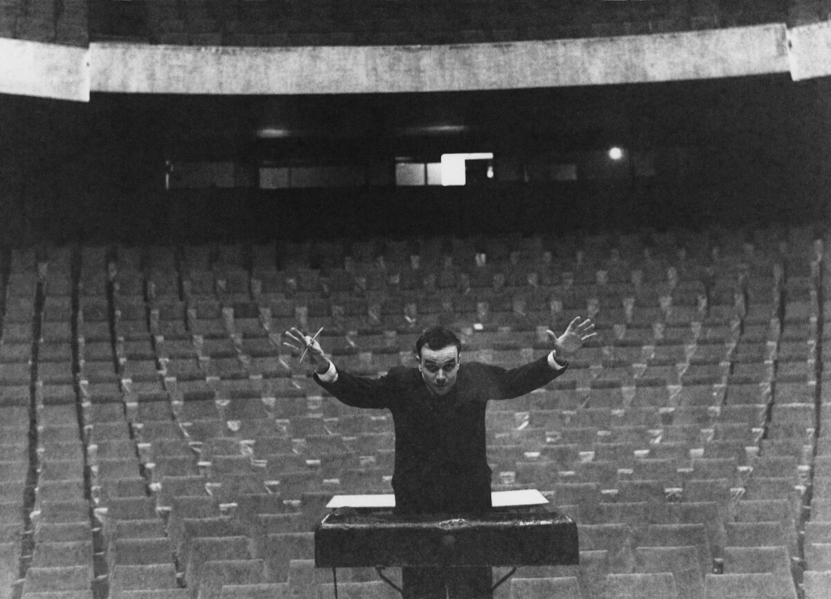 Yves Klein conducting his Symphonie Monoton in front of an imaginary orchestra, Gelsenkirschen's Opera House, 1959. © Yves Klein, ADAGP, Paris/ ARS, New York, 2016 © Photo Charles Wilp, BPK, Berlin.