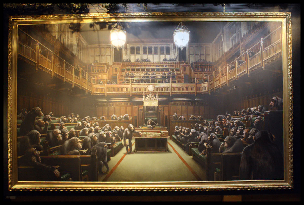 A painting by Banksy formerly titled Question Time, now Devolved Parliament, as it appeared in a 2009 exhibition at the Bristol Museum. Photo by Josh Blair, via Flickr.