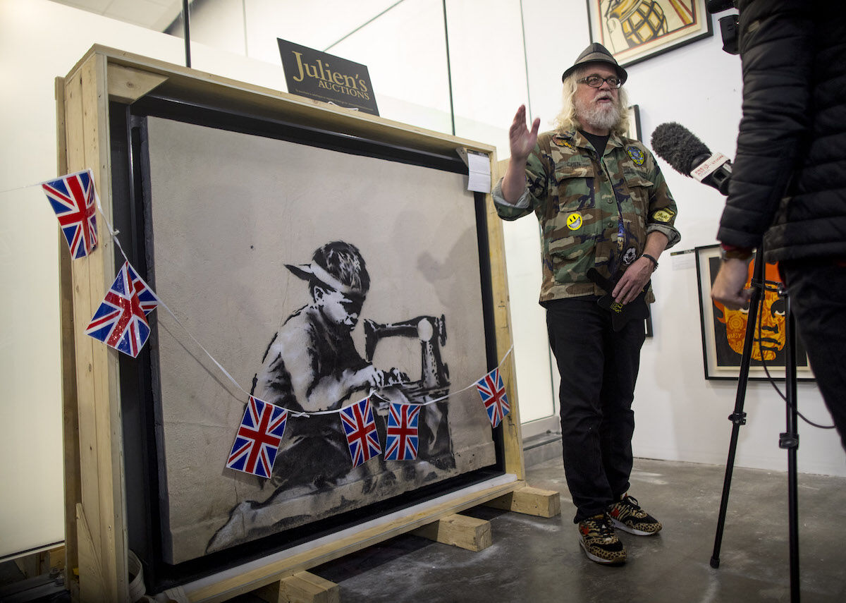Ron English standing in front of a Banksy mural he recently bought and plans to whitewash as an act of protest. Photo by Barbara Davidson/Getty Images.