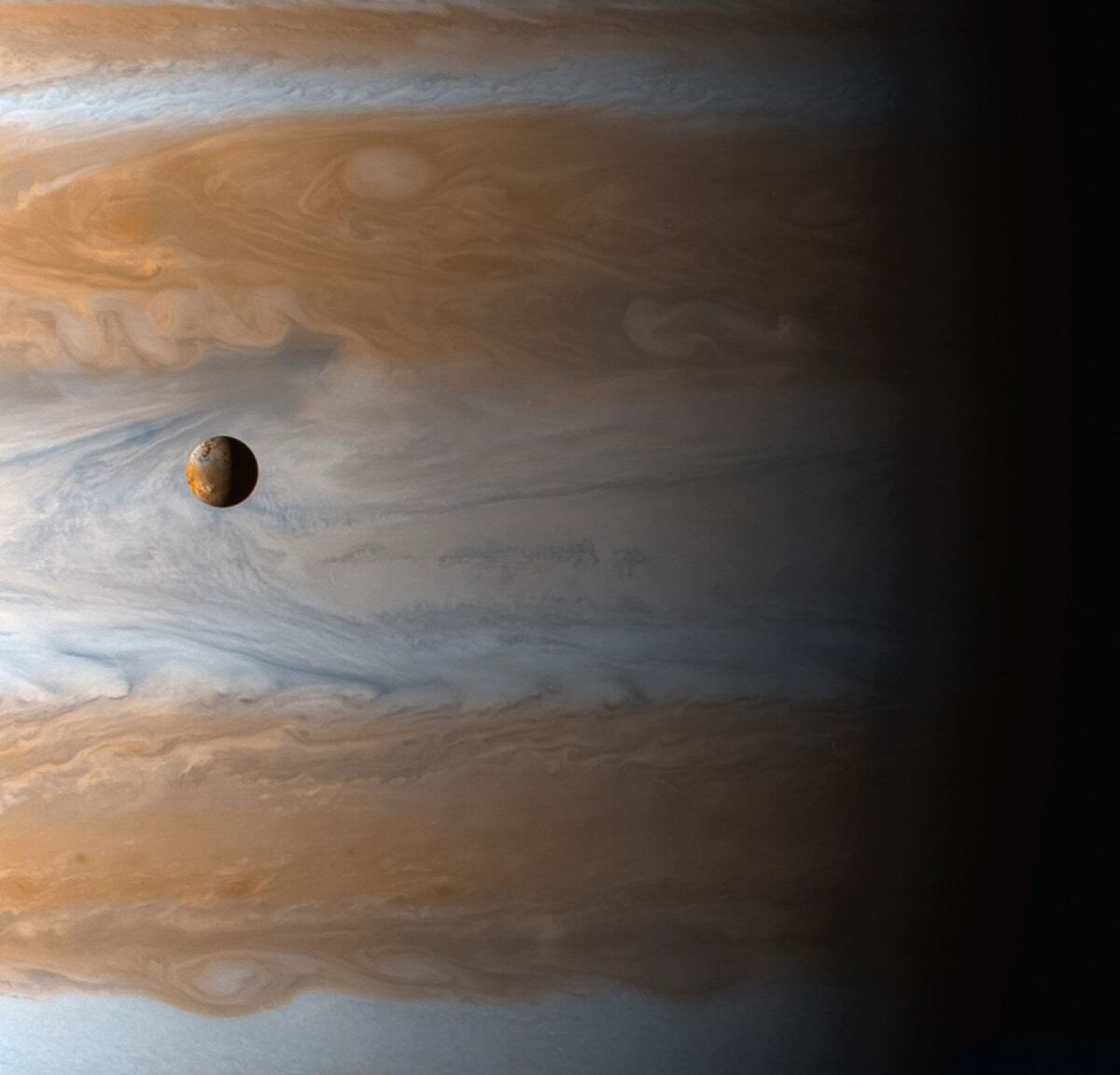 Jupiter's moon Io is dwarfed by the planet it orbits, as seen by the Cassini spacecraft en route to Saturn. Cassini's 13-year tour of the ringed planet changed the course of planetary exploration. © Courtesy of NASA.