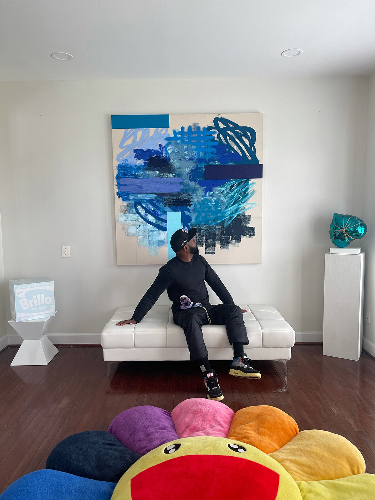 Portrait of Gambriel Wills with works, from left to right and top to bottom, by Daniel Arsham, Patrick Alston, Adam Parker Smith, and Takashi Murakami, 2021. Courtesy of Gambriel Wills.