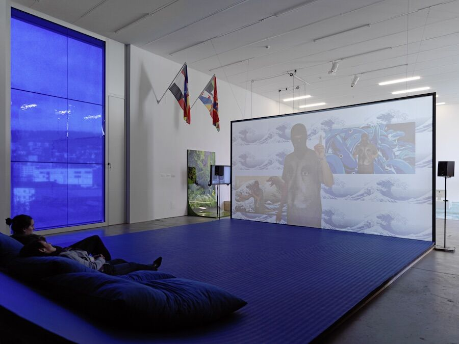 """Installation view of """"Filter Bubble,"""" an 89plus exhibition co-curated by Simon Castets and Hans Ulrich Obrist, at LUMA Westbau, Zürich, until February 14th, 2016. Photo by Stefan Altenburger. Pictured: Hito Steyerl, Liquidity Inc., 2014; James Bridle, Citizen Ex Flags 003  007, 2015; Ho Rui An, Screen Green, 2015."""