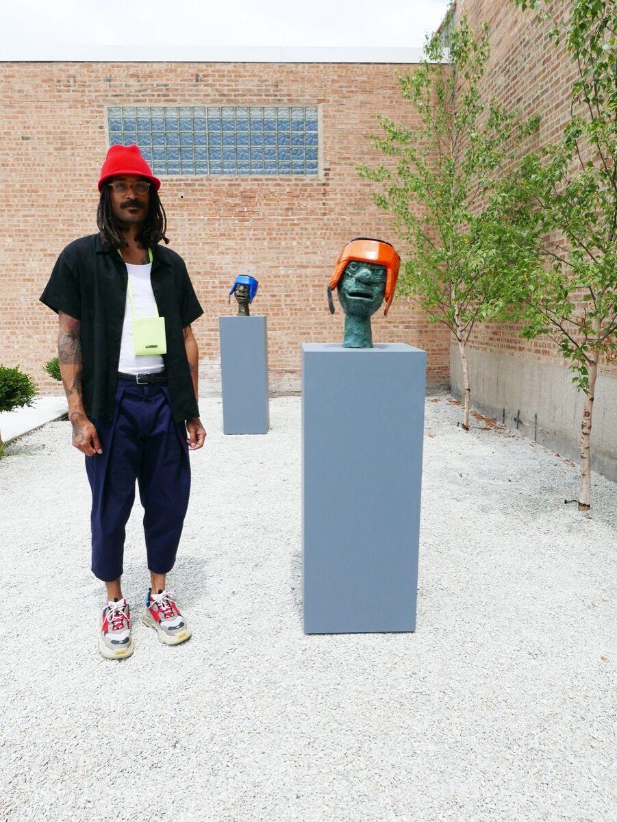 "Clotilde Jiménez with his sculpture, Orange Boxer, 2020, in ""The Contest"" at Mariane Ibrahim Gallery, 2020. Courtesy of Mariane Ibrahim Gallery."