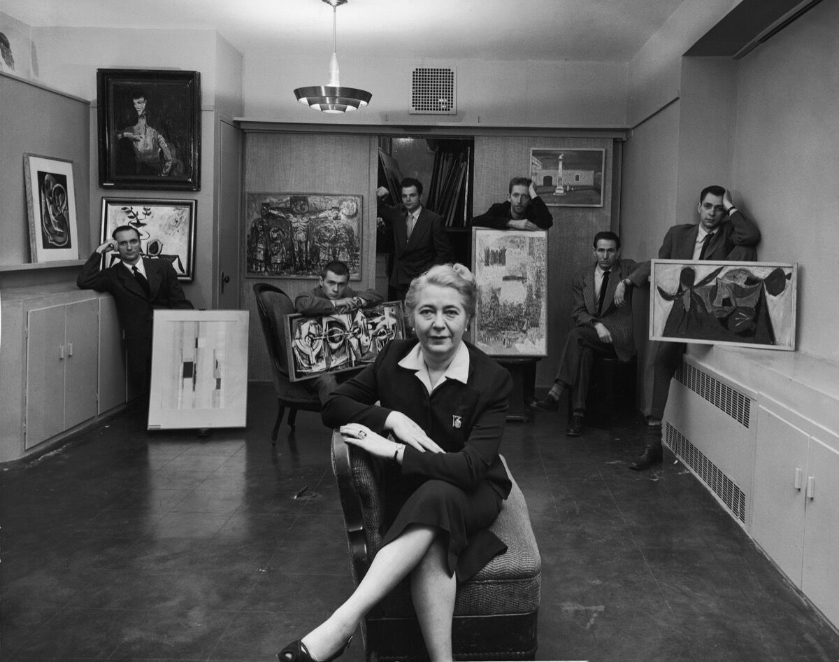 Edith Halpert at the Downtown Gallery, wearing the 13 watch brooch and ring designed for her by Charles Sheeler, in a photograph for Life magazine in 1952. She is joined by some of the new American artists she was promoting that year: Charles Oscar, Robert Knipschild, Jonah Kinigstein, Wallace Reiss, Carroll Cloar, and Herbert Katzman. Photo © Estate of Louis Faurer. Courtesy of the Jewish Museum.