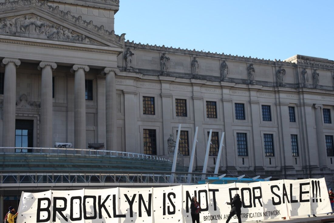 During protests organized by the Brooklyn Anti-Gentrification Network (BAN), demonstrators unfurled a 65-foot banner in front of the Brooklyn Museum. Photo by Isaac Kaplan.