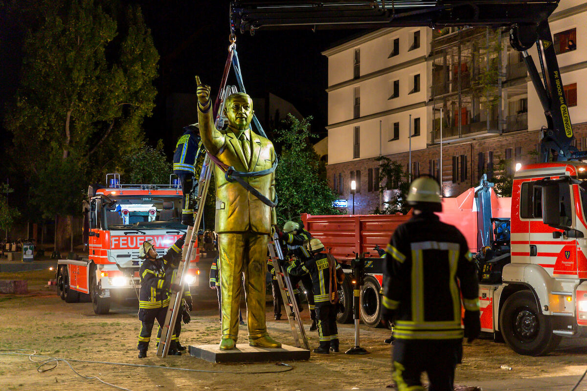 Fireworkers lift a 13-foot-tall golden statue of Turkish President Recep Tayyip Erdoğan to remove it late on August 28, 2018 in the western German town of Wiesbaden. Photo by Sebastian Stenzel/AFP/Getty Images.