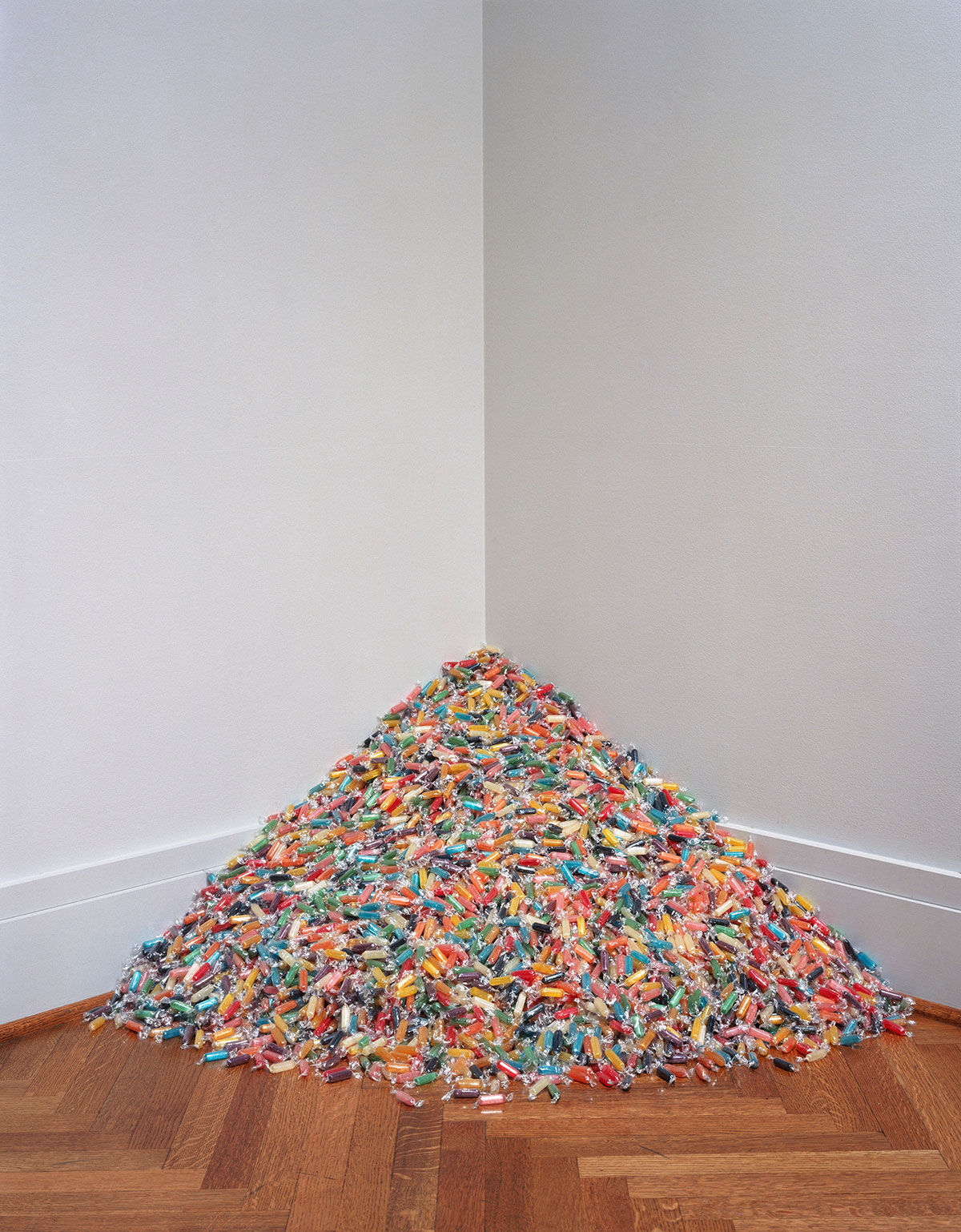 "Felix Gonzalez-Torres, ""Untitled"", 1992. Candies individually wrapped in variously colored cellophane, endless supply. Overall dimensions vary with installation. Original size: 2 x 48 x 48 in. Installation view: A Day Without Art. St. Louis Art Museum, St. Louis, MO. 29 Nov. – 3 Dec. 2002. Photographer: Robert Pettus. © The Felix Gonzalez-Torres Foundation. Courtesy of Andrea Rosen Gallery, New York."