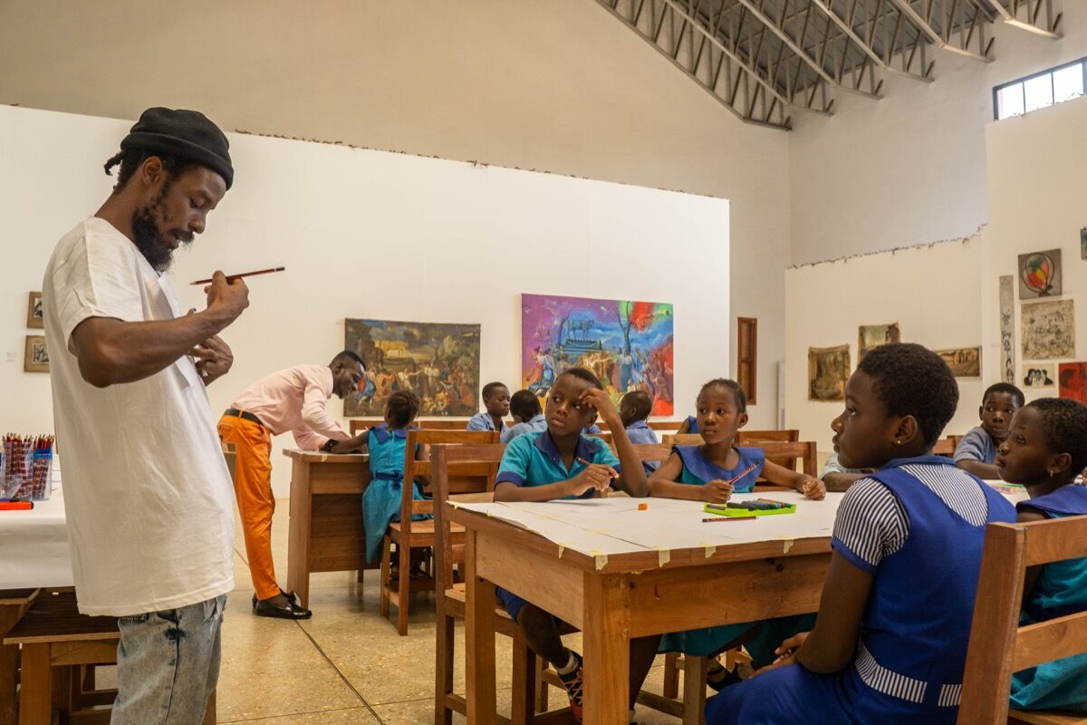 "Savannah Centre for Contemporary Art (SCCA) Tamale Artistic Director guiding students through a series of workshops as part of Ghanaian artist Galle Winston Kofi Dawson's retrospective, ""In Pursuit of something 'Beautiful', perhaps…,"" 2019–2020. Courtesy of SCCA Tamale."