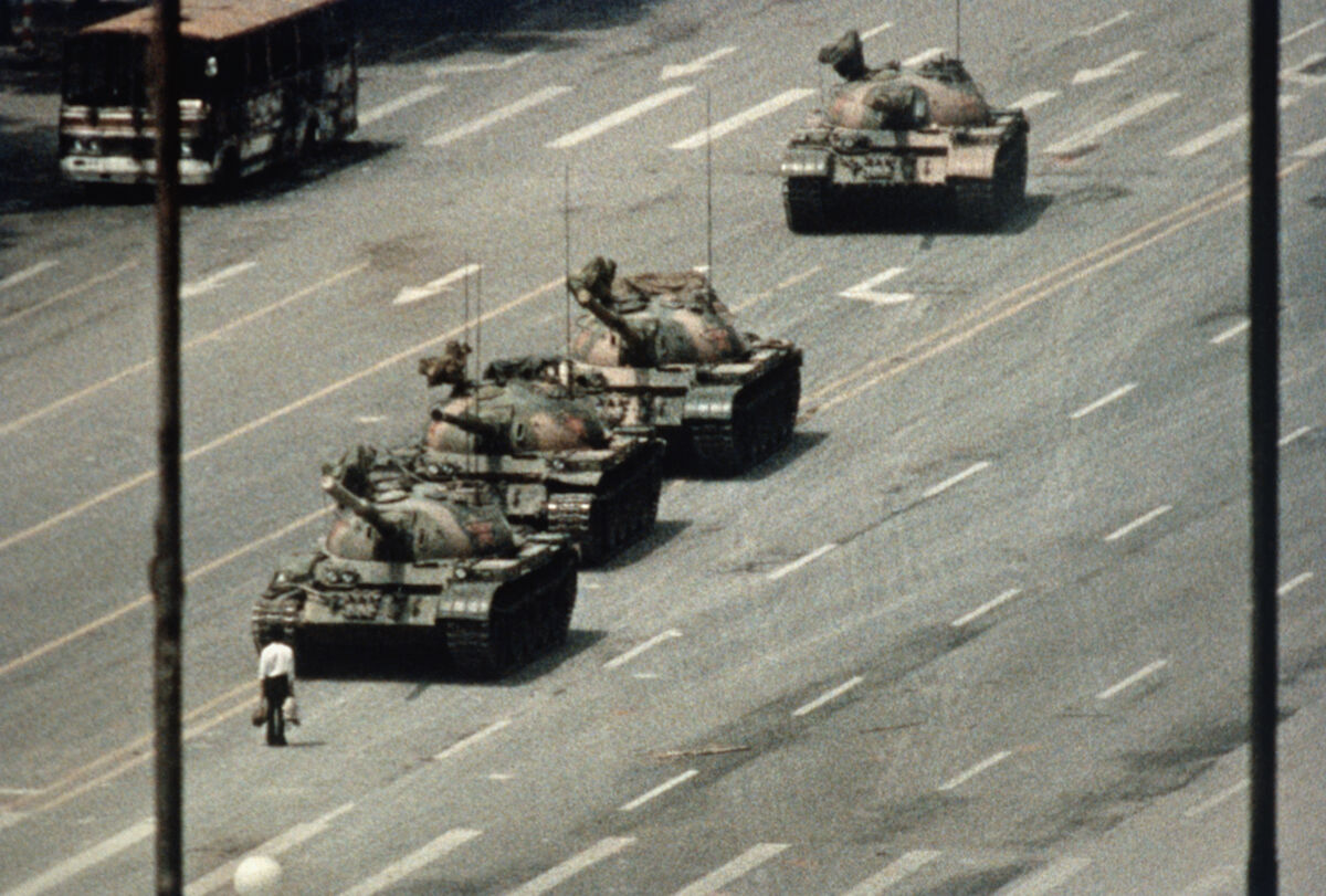 A Beijing demonstrator blocks the path of a tank convoy along the Avenue of Eternal Peace near Tiananmen Square. Photo by Bettmann via Getty Images.