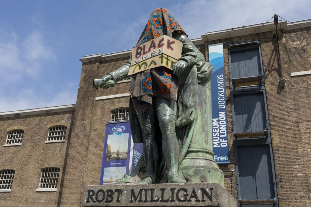 Statue of merchant slave owner Robert Milligan stands partially covered by Black Lives Matter activists outside the Museum of London's Docklands Museum on June 9, 2020, in London, United Kingdom. Photo by Richard Baker / In Pictures. Image via Getty Images.