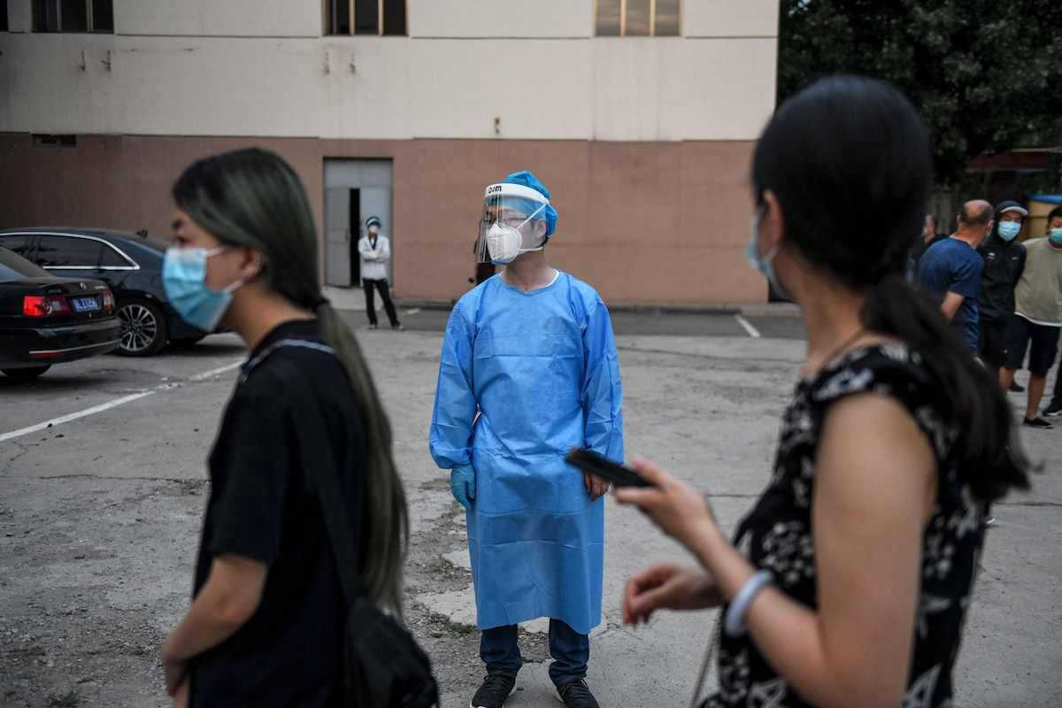 People who had their car number plates recorded in the area of the Xinfadi market where a new COVID-19 coronavirus cluster emerged last week, wait to do swab tests for the coronavirus as a medical worker stands nearby at a testing centre in Beijing on June 17, 2020. Photo by Greg Baker/AFP via Getty Images.