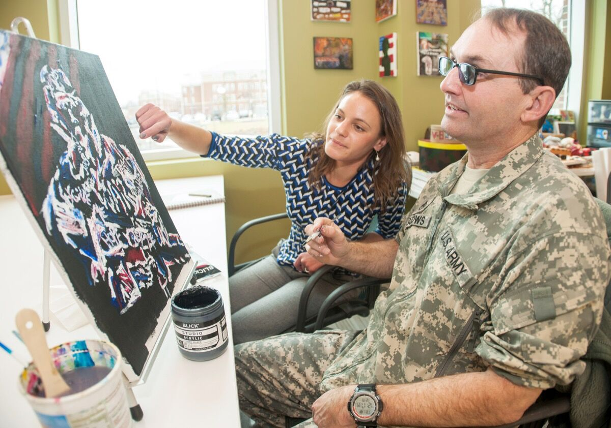 Army Staff Sgt. Jonathan Meadows and Jackie Biggs discuss a painting during an art therapy session at Fort Belvoir Community Hospital's traumatic brain injury clinic at Fort Belvoir, Va., Dec. 19, 2014.Photo by Marc Barnes. Courtesy the United States Department of Defense.