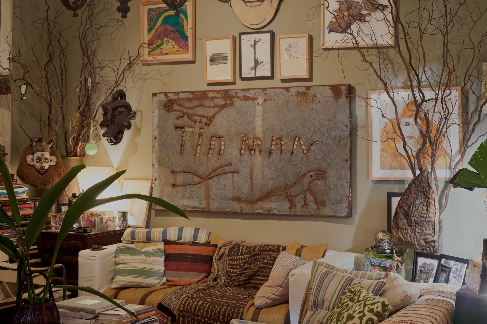 A sign made by Charlie Lucas from Alabama is the centerpiece in Fagaly's living room. At its edges, works by Tony Oursler, Trenton Doyle Hancock, and Jacqueline Humphries hang above couches that were formerly a part of Christian Marclay's The Clock (2010). Photo by Michael Adno for Artsy.