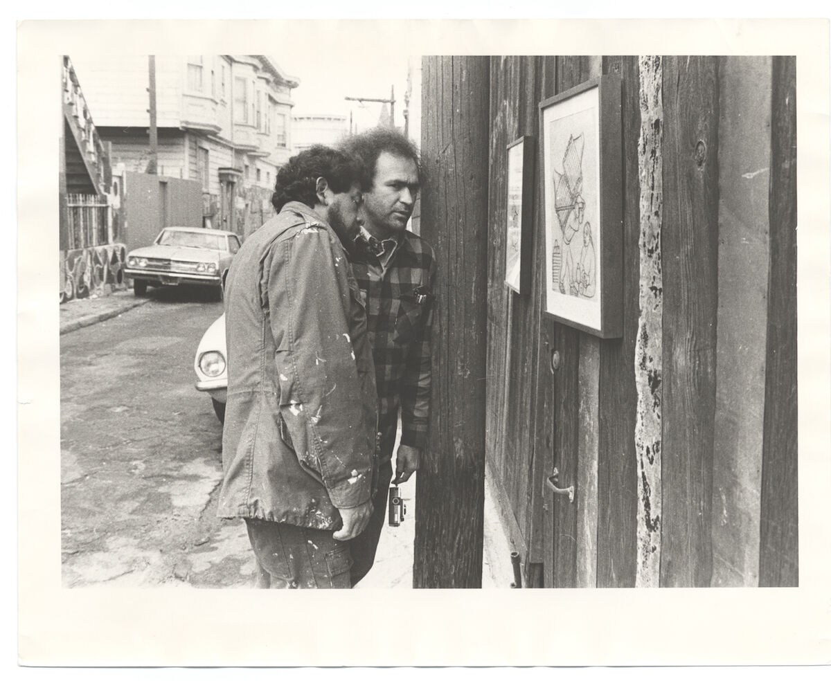 """Carlos Loarca and Rupert García in Balmy Alley, San Francisco, viewing works from an extension of the Galería de la Raza exhibition """"Rivera, Orozco, Siquieros: Original Drawings and Prints."""" Photographer unknown. Tomás Ybarra-Frausto research material on Chicano art. CourArchives of American Art, Smithsonian Institution."""
