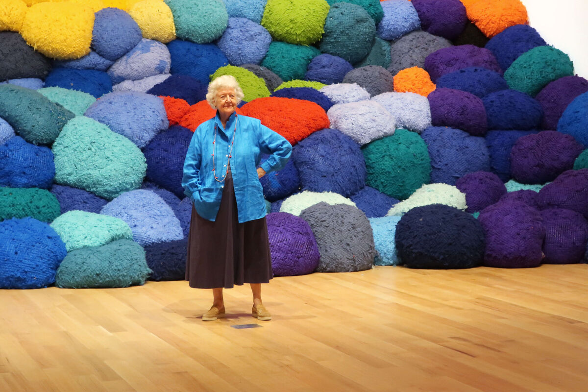 "Portrait of Sheila Hicks in front of Escalade Beyond Chromatic Lands (2016-2017), ""Campo Abierto (Open Field)"" at The Bass Museum of Art, 2019. Photo by Mudita."