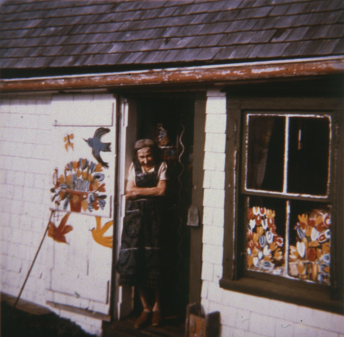 Maud Lewis in front of her house, 1961. Photo by Cora Greenaway. Courtesy of the Art Gallery of Nova Scotia.