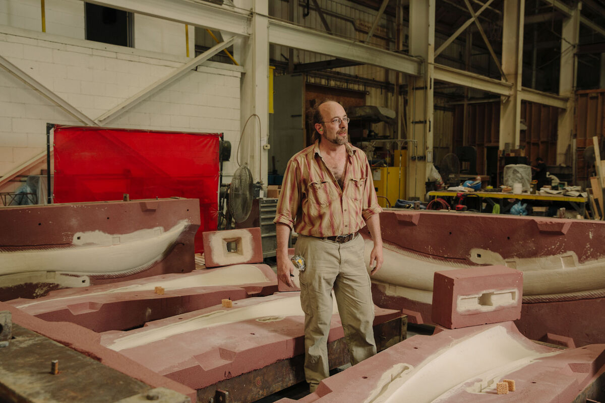 Sand molder Morgan Donahue, surrounded by sand molds for a sculpture by Christopher Curtis.  Photo by Ricky Rhodes for Artsy.