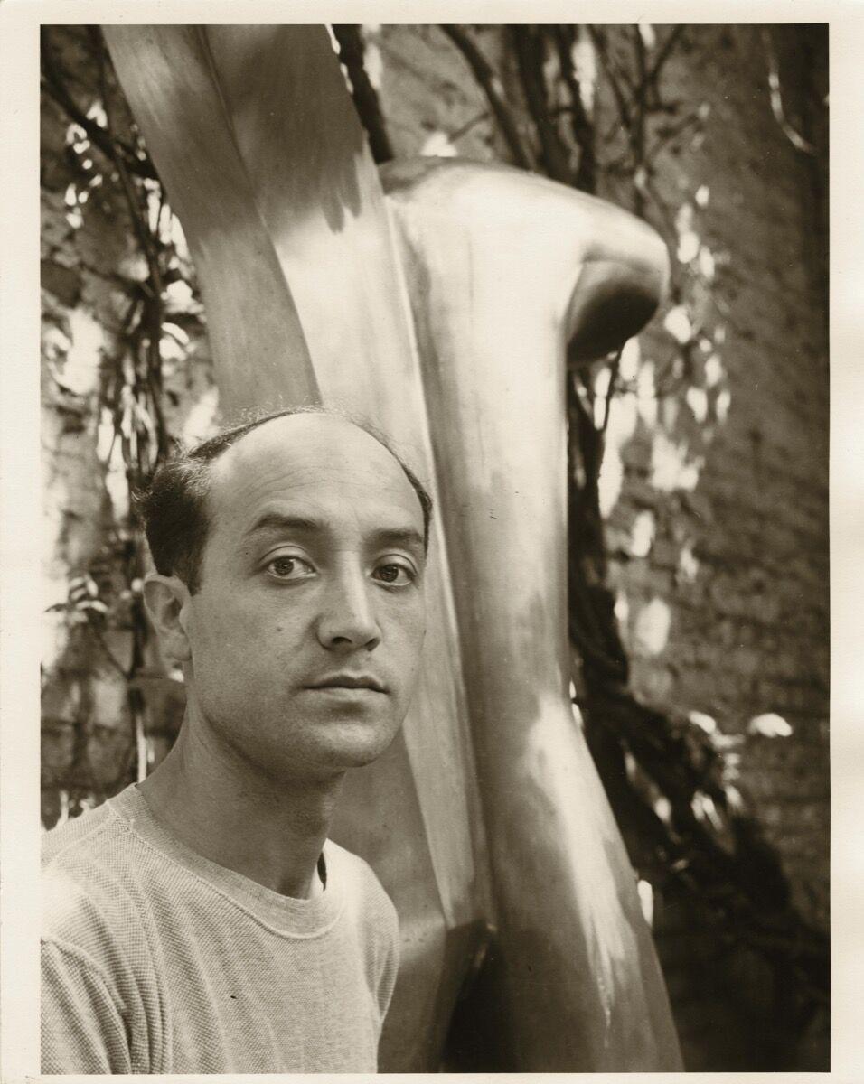 Isamu Noguchi in the courtyard of his MacDougal Alley Studio with Man Aviator, 1943-49. © The Isamu Noguchi Foundation and Garden Museum, New York / ARS.