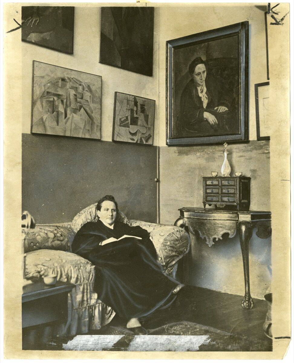 Gertrude Stein sitting on a sofa in her Paris studio, 1930. Image by World Wide Photos, via Wikimedia Commons.