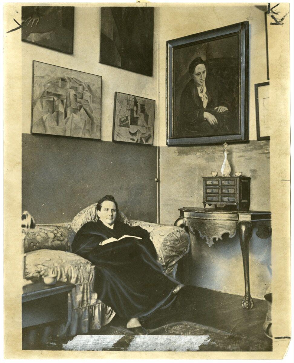 Gertrude Stein sentada en un sofá en su estudio de París, 1930. Imagen de World Wide Photos, vía Wikimedia Commons.