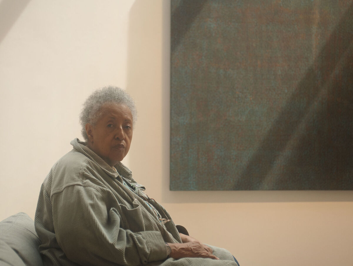 Howardena Pindell with her work at Garth Greenan Gallery by Alex John Beck for Artsy.