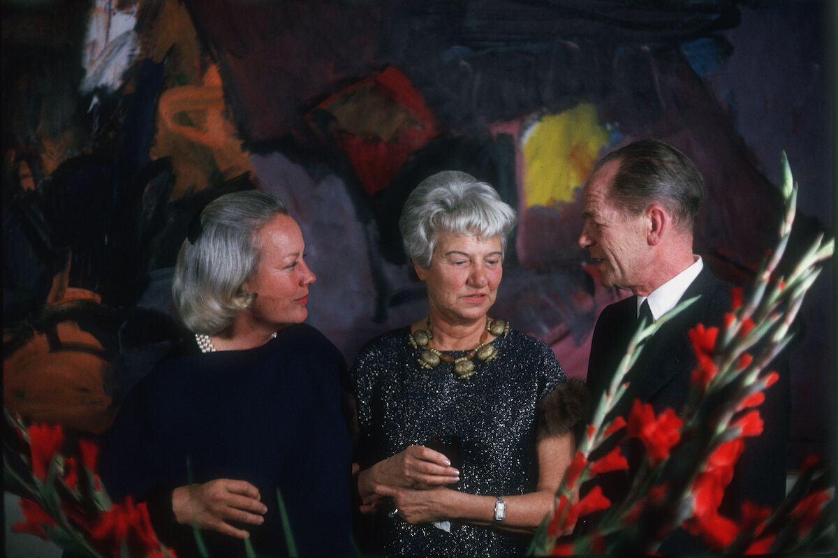 Fay Emerson, Peggy Guggenheim, and Martyn Coleman standing in front of Grace Hartigan's painting, Ireland, 1958. Photo by David Lees/Corbis/VCG via Getty Images.