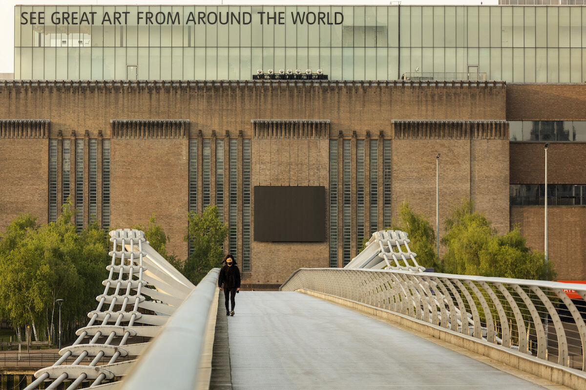 A woman wearing a face mask crosses Millenium Bridge in front of Tate Modern in London. Photo by Barry Lewis/InPictures via Getty Images.