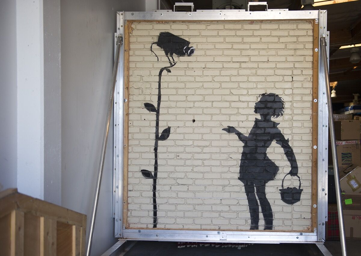 A work by Banksy titled Flower Girl is seen at Julien's warehouse in Los Angeles, California August 21, 2013. Photo by Robyn Beck/AFP/Getty Images.