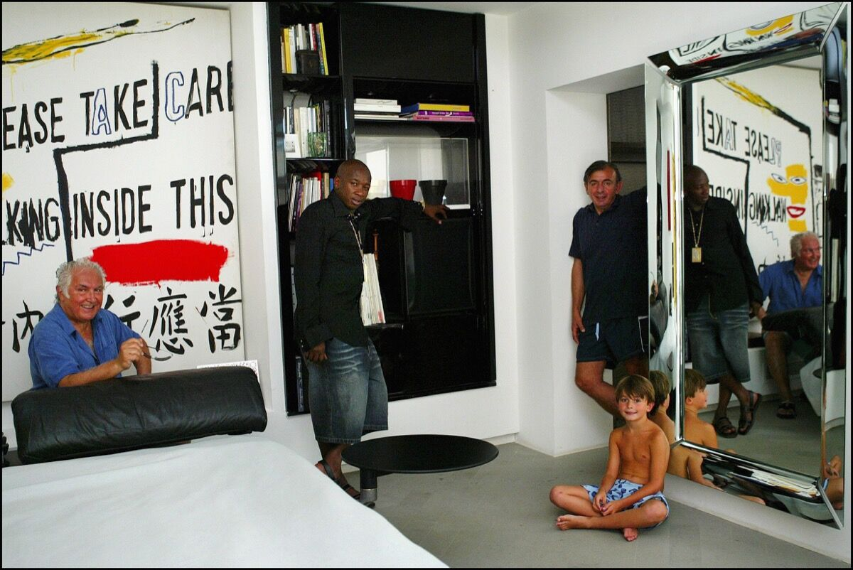 From left to right: Tony Shafrazi in front of art by Andy Warhol and Jean Michel Basquiat, with Mohamed Dia, Enrico Navarra, and Enrico's son Doriano at Navarra's villa, 2003. Photo by Eric TRAVERS/Gamma-Rapho via Getty Images.
