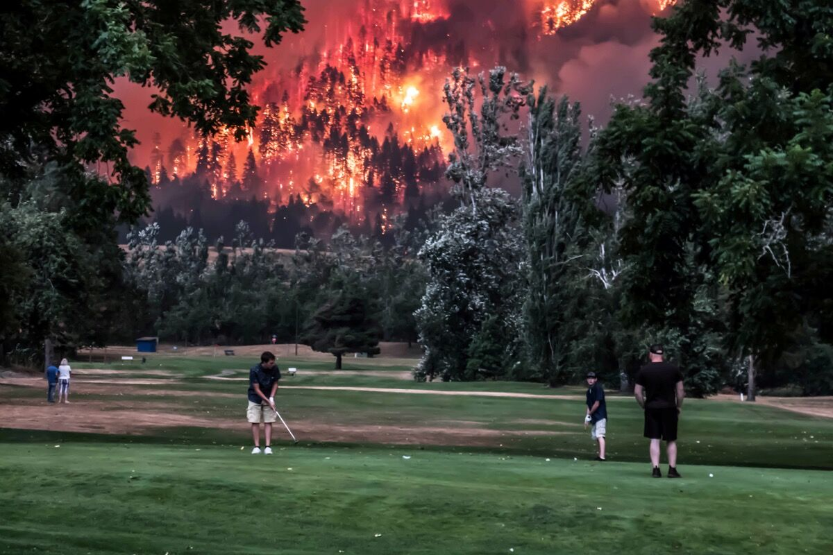 The Eagle Creek wildfire burns as golfers play at the Beacon Rock Golf Course in North Bonneville, Washington, U.S. September 4, 2017. Picture taken on September 4, 2017. REUTERS/Kristi McCluer.