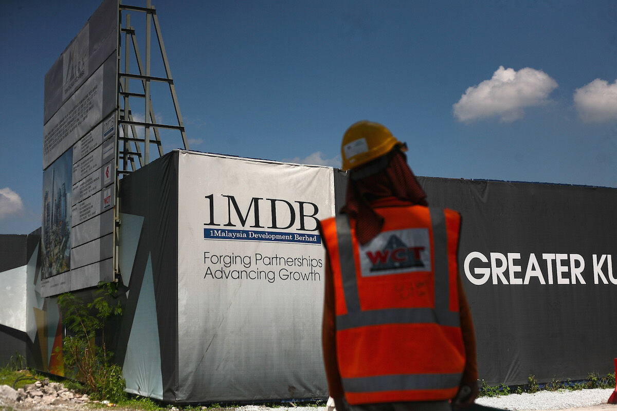 A construction worker stands near the 1Malaysia Development Berhad (1MDB) billboard at a construction site on June 5, 2015 in Kuala Lumpur, Malaysia. Photo by Mohd Samsul Mohd Said/Getty Images.