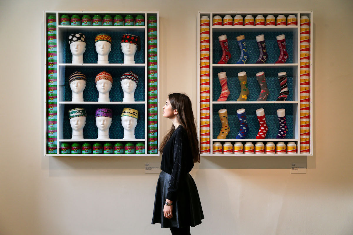 A gallery assistant poses next to works by Hassan Hajjaj at the 2017 edition of the 1-54 Contemporary African Art Fair in London. Photo by Daniel Leal-Olivas/AFP via Getty Images.
