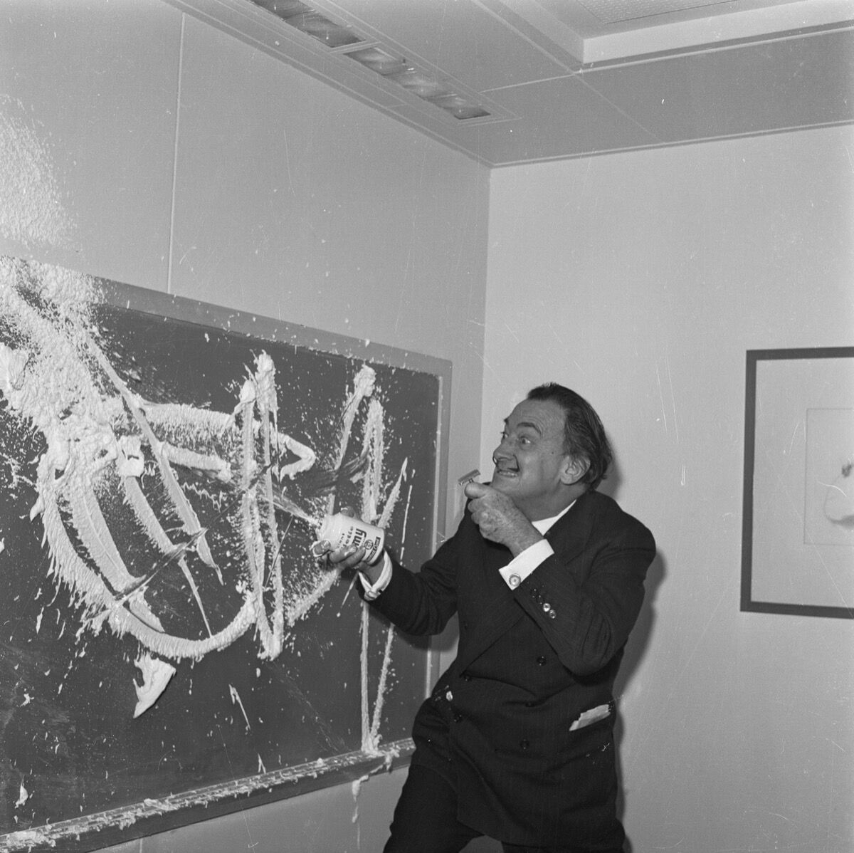 Salvador Dali paints with shaving cream on the blackboard of the children's playroom on the S.S. United States. Image via Getty Images.
