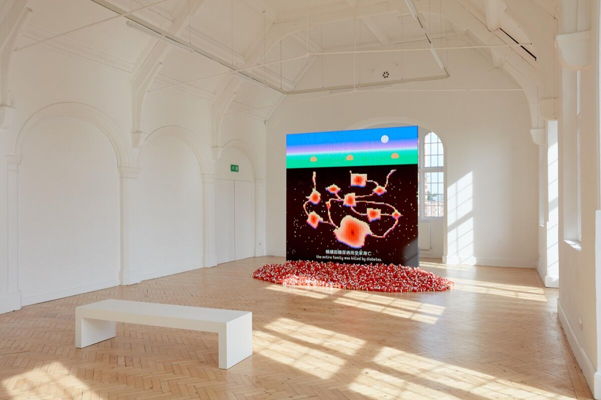 "Installation photo of Dear, Can I Give You a Hand?, 2018, film, and The Ha Ha Ha Online Cemetry Limited, 2019, toy dentures, in ""Wong Ping: Heart Digger,"" at the Camden Arts Centre, 2019. Artwork © Wong Ping. Photo by Luke Walker. Courtesy of the Camden Arts Cent"