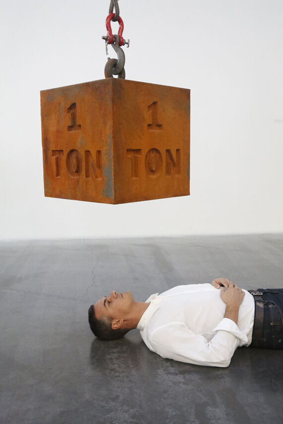 """Massimiliano Gioni with 1 Ton Crane Truck (2009) by Chris Burden, on view as part of """"Chris Burden: Extreme Measures"""" (2013–14). Courtesy New Museum, New York. Photo: Jesse Untracht-Oakner"""