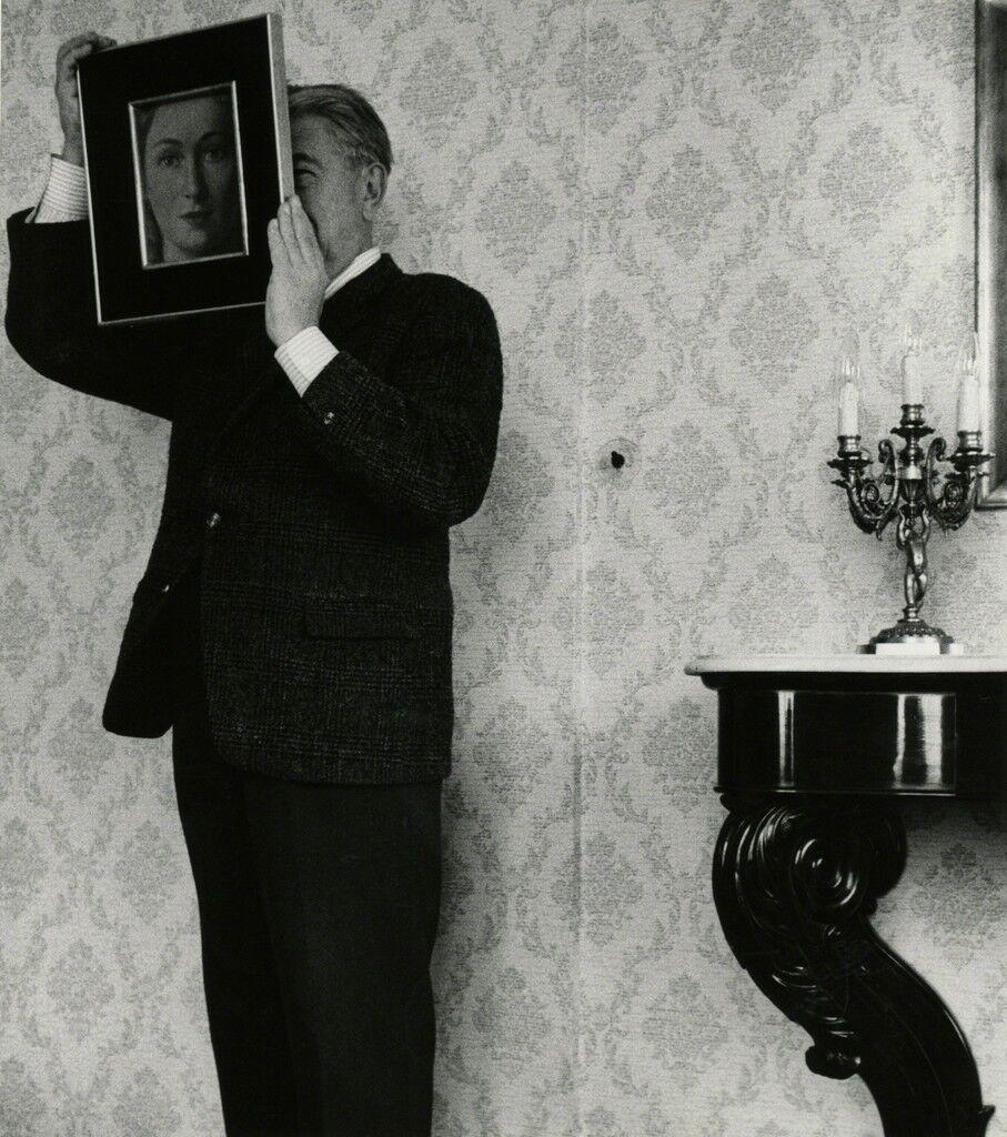 """René Magritte posant avec """"La Ressemblance"""" (partie de L'évidence éternelle"""" (1954)"""