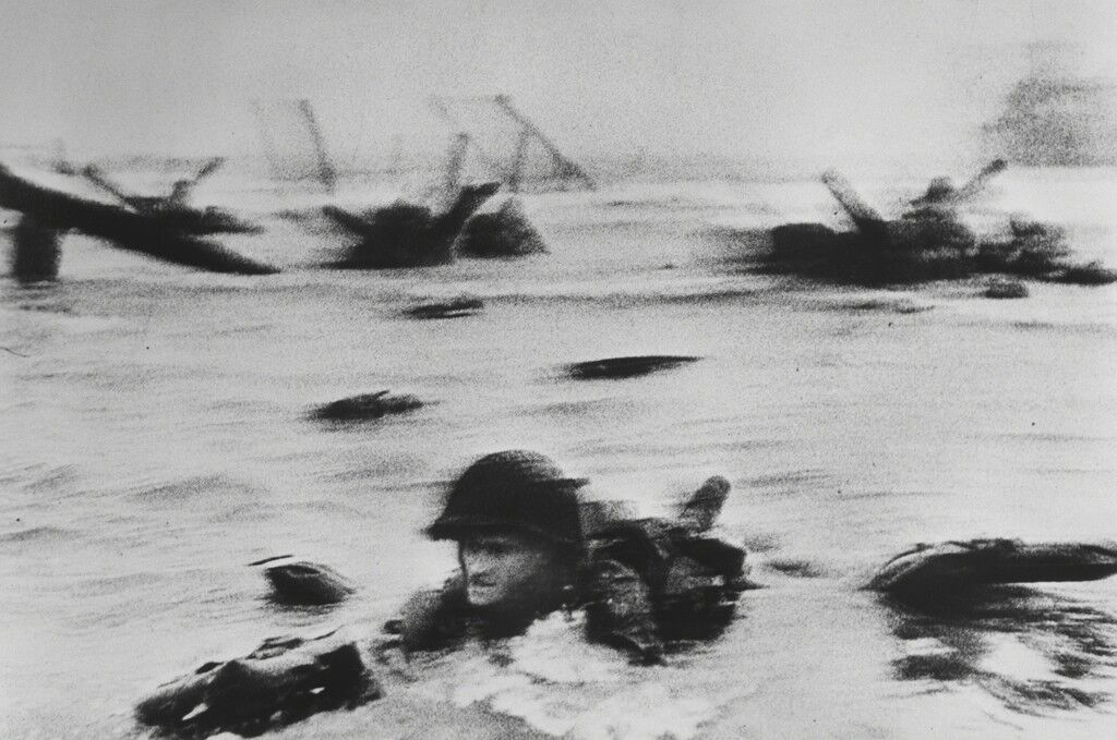 Image result for Robert Capa's most famous photograph shows an American soldier moving through the water