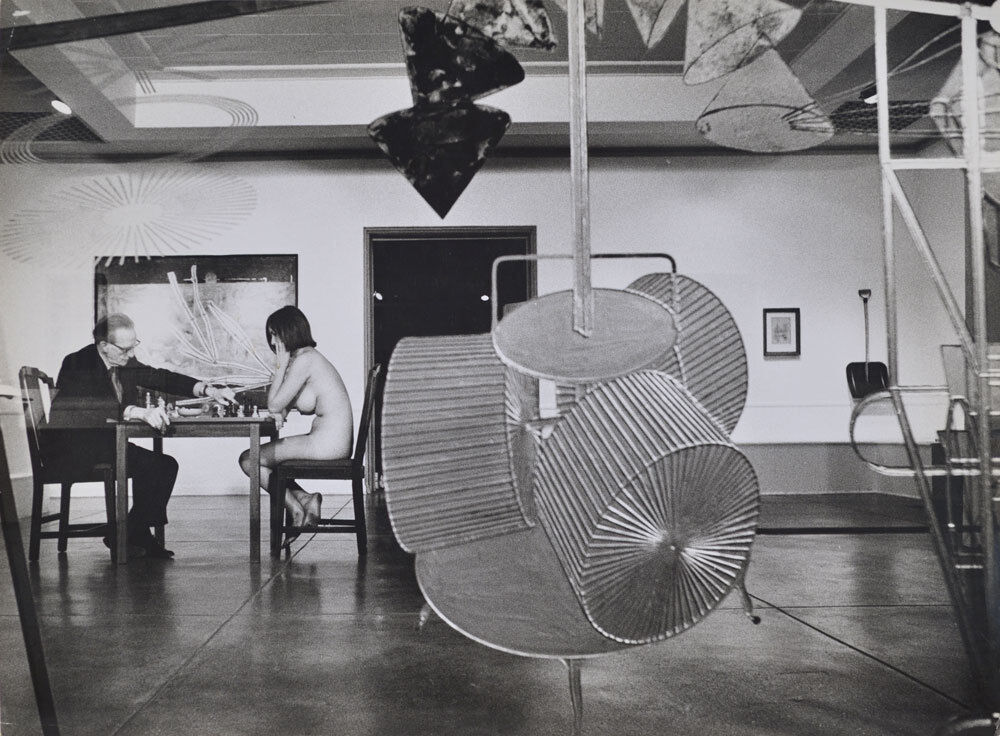Duchamp making a chess move in distance, Duchamp Retrospective, Pasadena Art Museum,