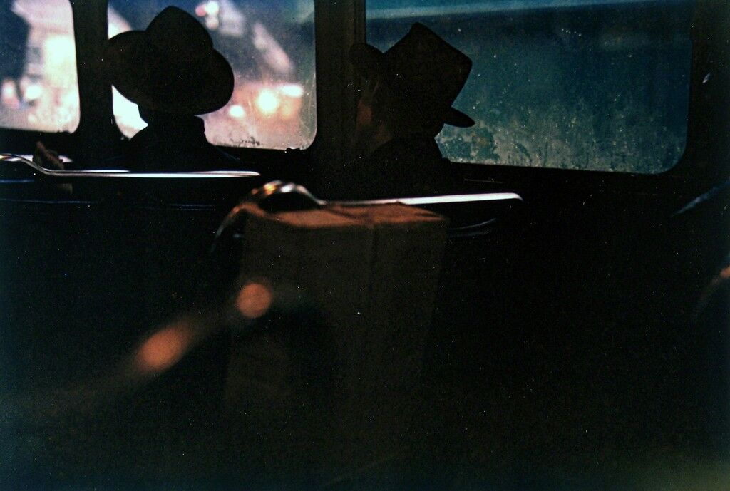 Untitled (two men in hats on train at night)