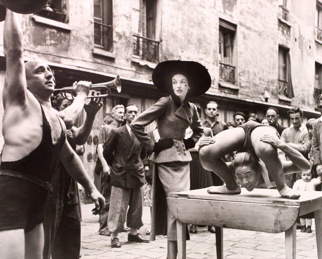Elise Daniels con artistas callejeros, Traje de Balenciaga, Le Marais, París, agosto de 1948