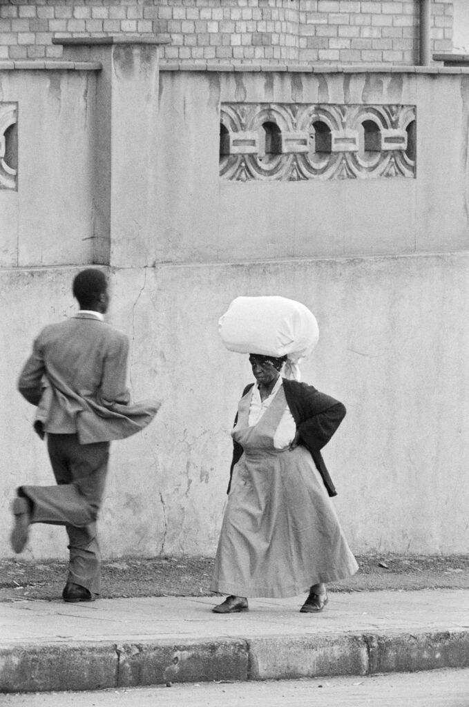 Anna Lebako, a washerwoman from Soweto carrying the week's laundry to a white suburban family, Harrow Road
